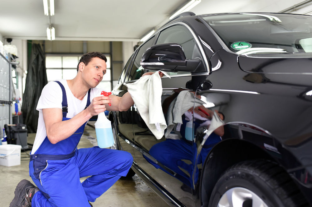 guy doing car exterior detailing