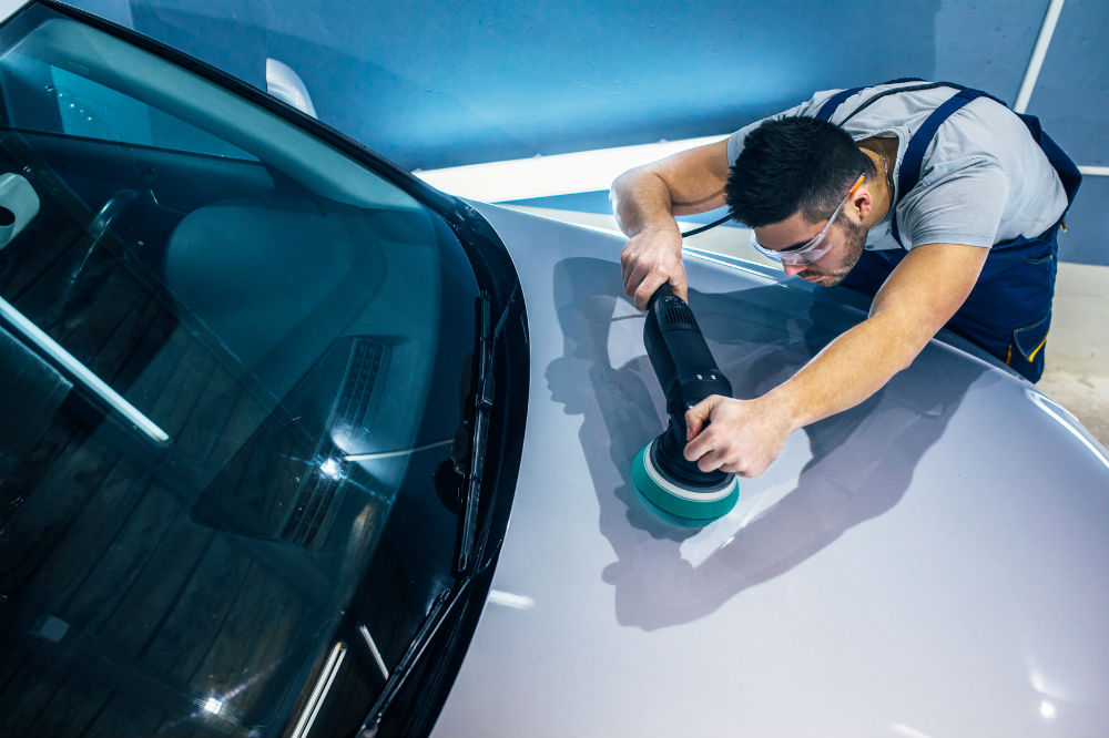 guy carefully polishing car