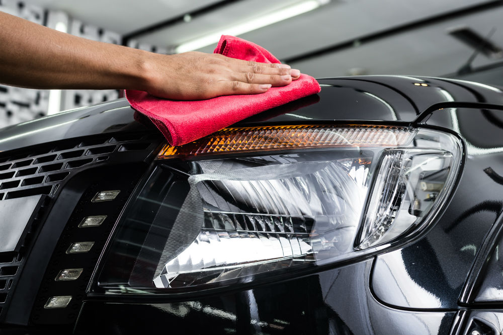 guy with microfiber towel wiping the car