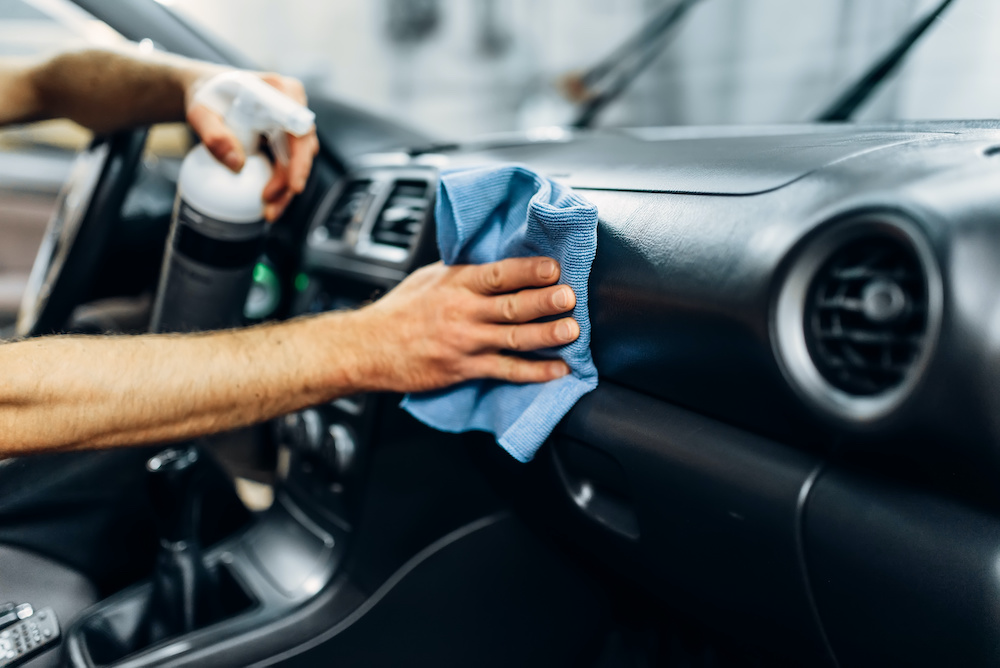 guy using polishing spray to car interior