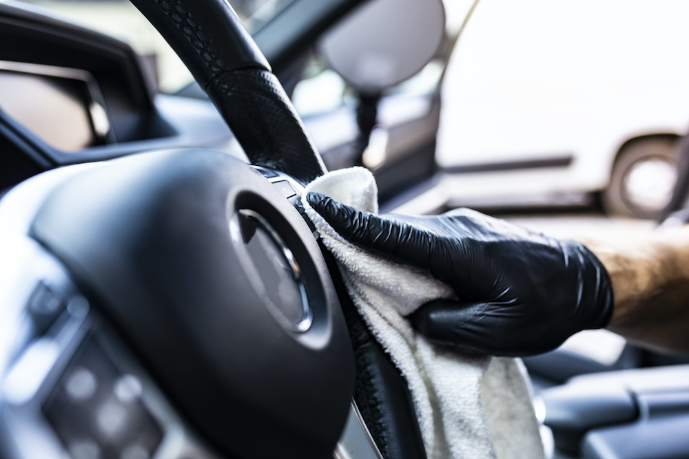 guy wiping car steering wheel with microfiber towel